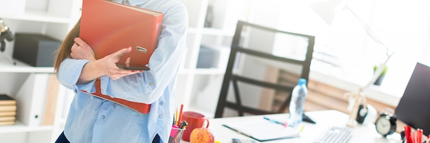 Una niña en la oficina está de pie, apoyada en una mesa, y sostiene un teléfono y una carpeta con documentos.