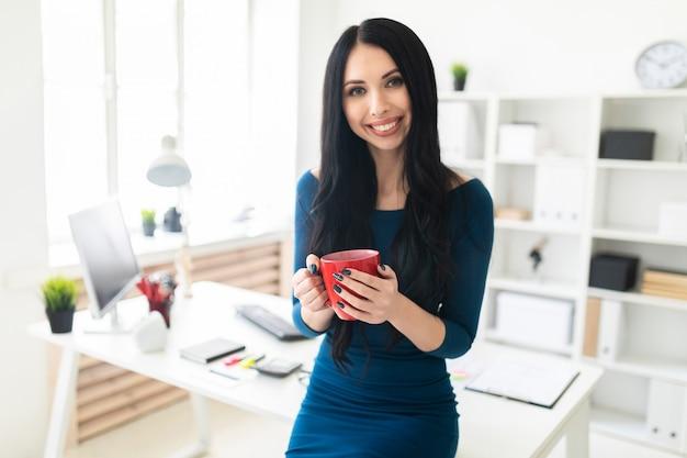 Una niña en la oficina se sentó en la mesa y sostenía una taza roja en sus manos.