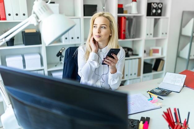 Una niña en la oficina se sienta en un escritorio con un teléfono en la mano y habla por unos auriculares.
