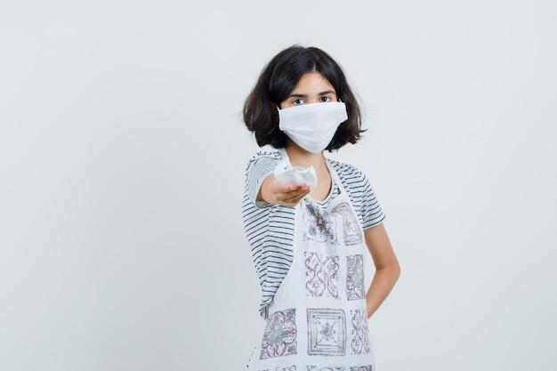Niña ofreciendo máscara médica en camiseta, delantal