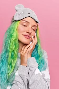 Niña con los ojos cerrados toca la cara suavemente ve dulces sueños mientras toma una siesta usa antifaz en la frente pijama cómodo se ha teñido el cabello de colores aislado en la pared rosa