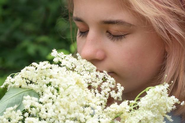 Niña oliendo flores de saúco en el jardín