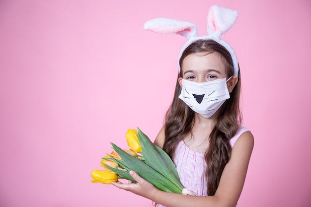 Niña con orejas de conejo de pascua y vistiendo una mascarilla médica sostiene un ramo de tulipanes en sus manos sobre un fondo de estudio rosa