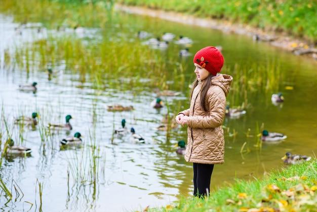 La niña de la orilla alimentando a los patos