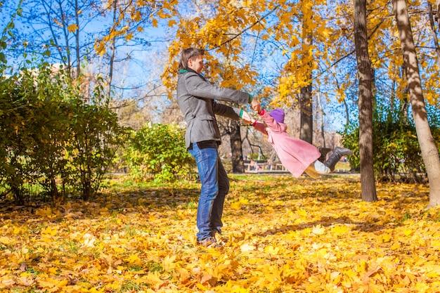 Niña con padre feliz divirtiéndose en el parque otoño en un día soleado