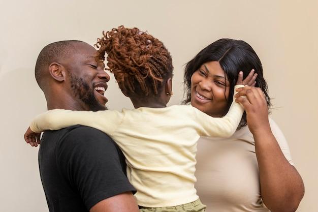 Niña y padres felices de tiro medio