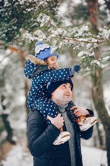 Niña con padres jugando en un parque de invierno