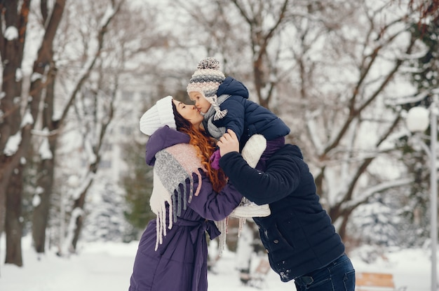 Niña con padres en un parque de invierno