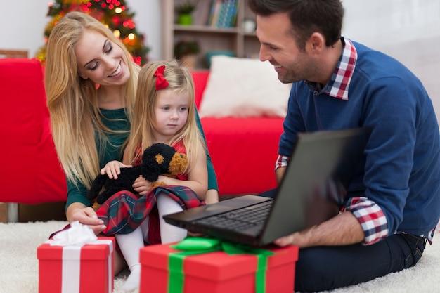 Niña con padres usando laptop en navidad