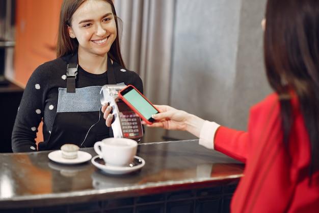 Niña pagando su café con leche con un teléfono inteligente con tecnología pay pass sin contacto