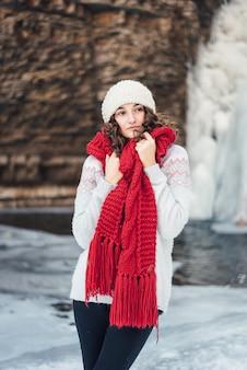Niña en un pañuelo rojo en invierno cerca de la cascada