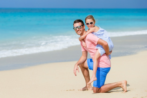 Niña y papá feliz divirtiéndose durante las vacaciones en la playa