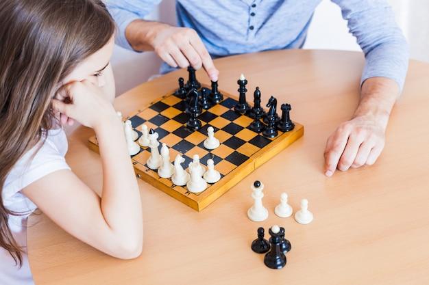 Niña y papá juegan un juego en casa, ajedrez, rompecabezas para el desarrollo del cerebro, inteligencia mental