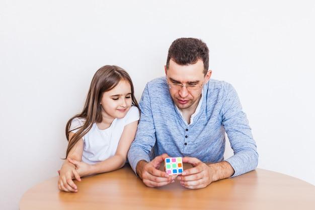Niña y papá juegan un juego en casa, el cubo de rubik, rompecabezas para el desarrollo del cerebro, inteligencia mental