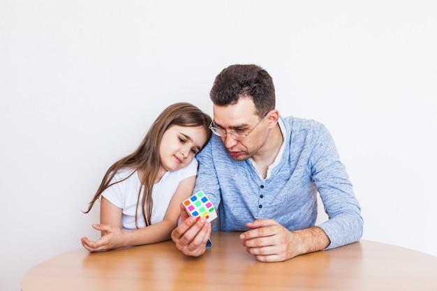 Niña y papá juegan un juego en casa, el cubo de rubik, un rompecabezas para el desarrollo del cerebro