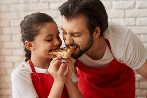 Niña y papá que prueban la rebanada de la pizza con la mordedura.