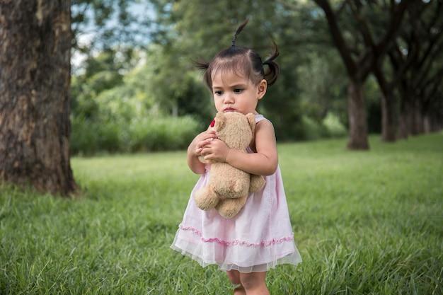 Niña parada sola debajo del árbol, sola con su muñeca