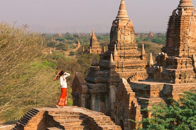 Una niña con un paraguas birmano se encuentra en la parte superior de la pagoda en bagan en medio del sol poniente y numerosas pagodas.