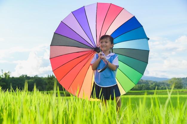 Niña bajo el paraguas de colores en la escena del campo de arroz.