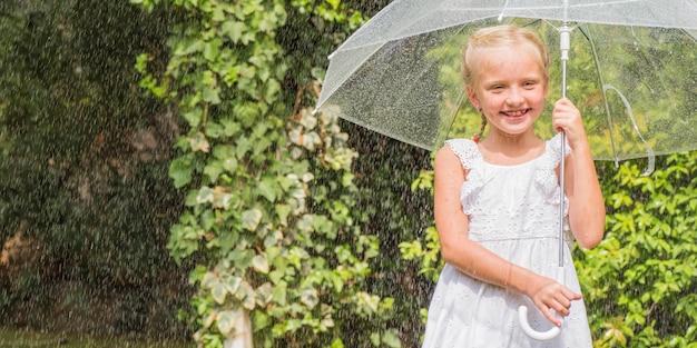Niña con paraguas jugando bajo la lluvia.