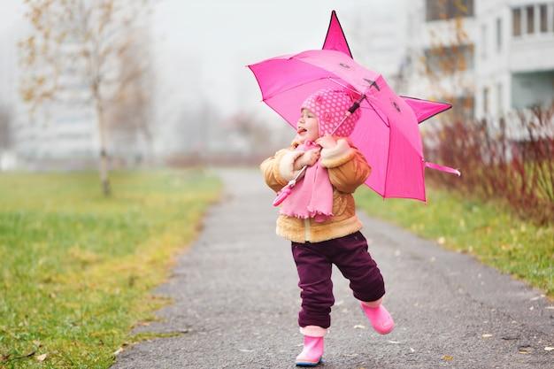 La niña bajo un paraguas en el otoño.