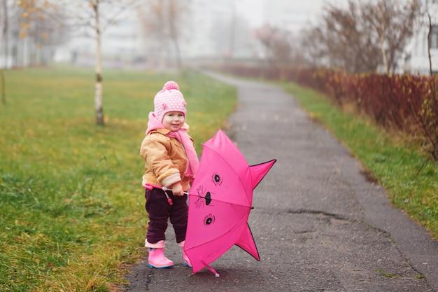 La niña con un paraguas en el otoño.