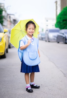 Niña con paraguas de pie en el aparcamiento listo para volver a la escuela en llover día