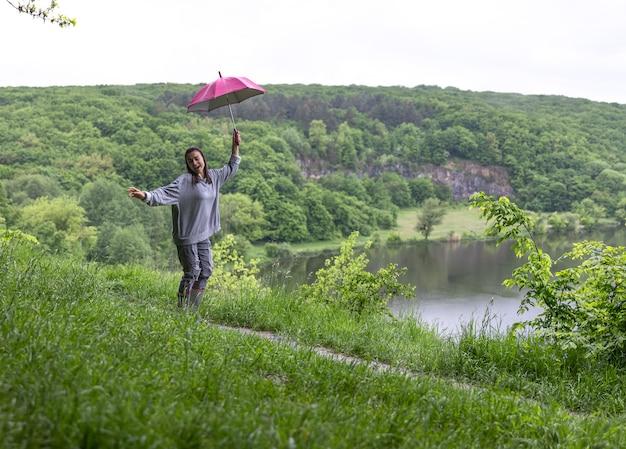 Una niña bajo un paraguas saltando cerca de un lago en una zona montañosa en tiempo lluvioso.