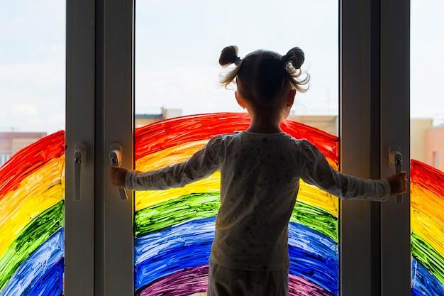 Niña en la pared de la pintura del arco iris en la ventana. ocio para niños en casa. apoyo visual positivo durante la cuarentena del coronavirus pandémico covid-19 en el hogar.