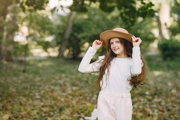 Niña en un parque de pie en un parque con un sombrero marrón