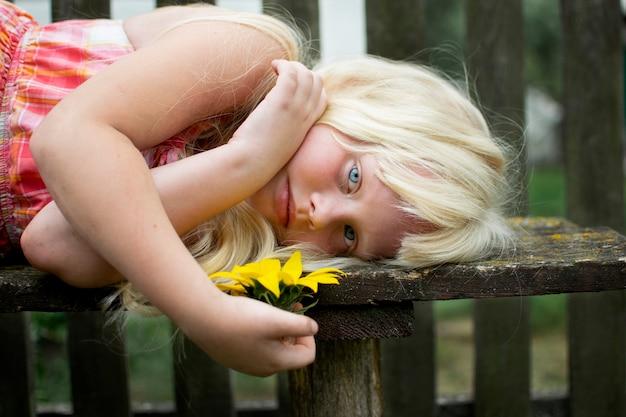 Una niña pasa el fin de semana en el pueblo. verano, vegetación, cielo azul. valla de madera