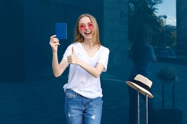 Una niña con un pasaporte con gafas rosas y una camiseta blanca sonriendo en un viaje de fondo azul