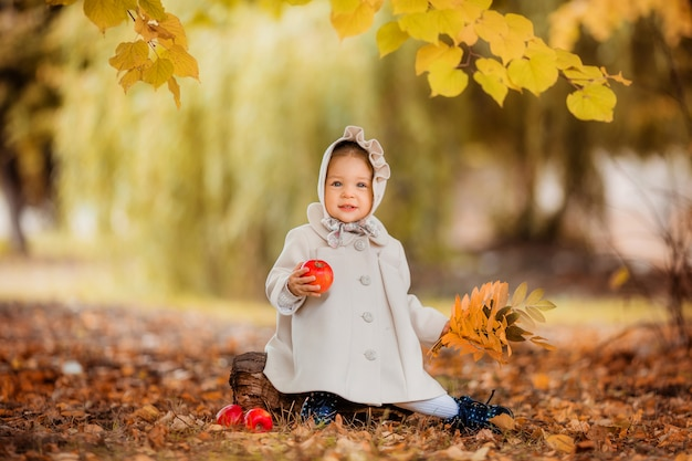 Niña en un paseo en el parque otoño