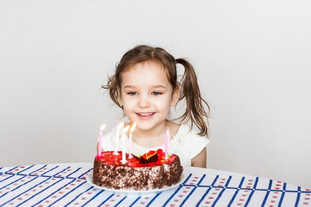Niña y pastel de cumpleaños, apaga velas, pide un deseo, pastel y velas, regalos de cumpleaños, familia, mamá y papá