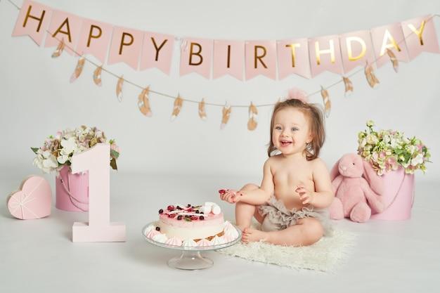 Niña con un pastel de cumpleaños, sesión de fotos de bebé de 1 año