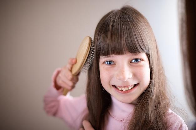 Niña con pecas y ojos azules peinándose el pelo.