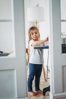 Niña con el pelo largo en ropa de casa de pie en la mesa y jugando, efecto de espiar desde las puertas