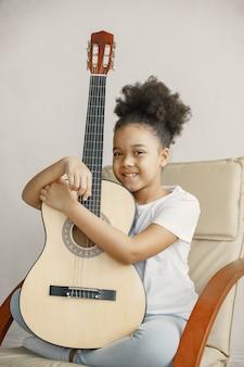 Niña con pelo rizado. aprendiendo a tocar la guitarra. niña en una silla.