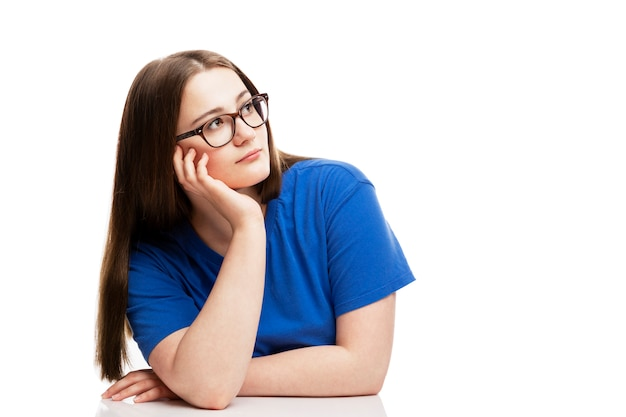 Una niña pensativa con gafas y una camiseta azul se sienta apoyando su cabeza en su mano. . espacio para texto.