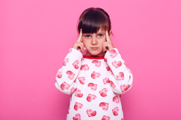 Niña pensativa mirando a cámara, piensa en cosas importantes, manteniendo los dedos cerca de las sienes, siendo pensativa y concentrada, aislada sobre la pared rosa.