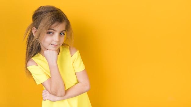 Niña pensativa en vestido en fondo amarillo