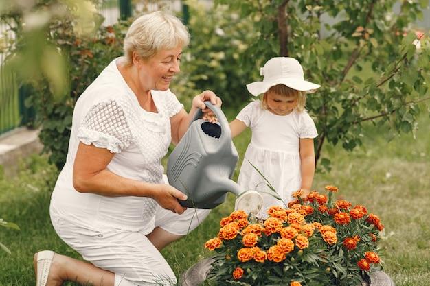 Niña pequeña con abuela senior de jardinería en el jardín del patio trasero. niño con sombrero blanco.