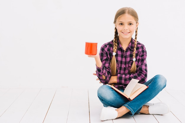 Niña pequeña adorable leyendo un libro y sosteniendo una taza
