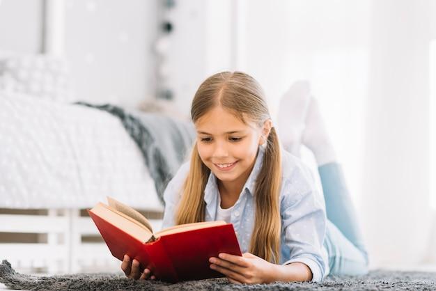 Niña pequeña adorable leyendo un libro