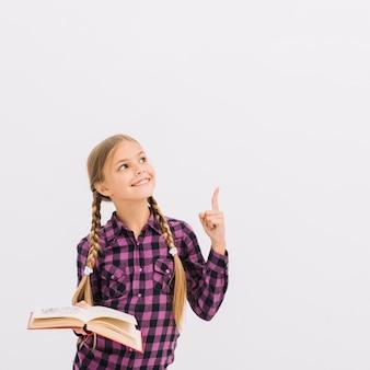 Niña pequeña adorable con un libro señalando hacia arriba