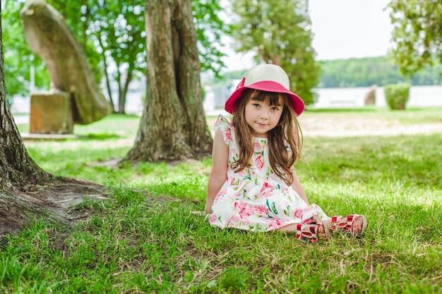 Niña pequeña adorable posando en el parque