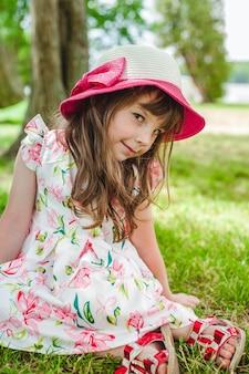 Niña pequeña adorable sonriendo en un parque