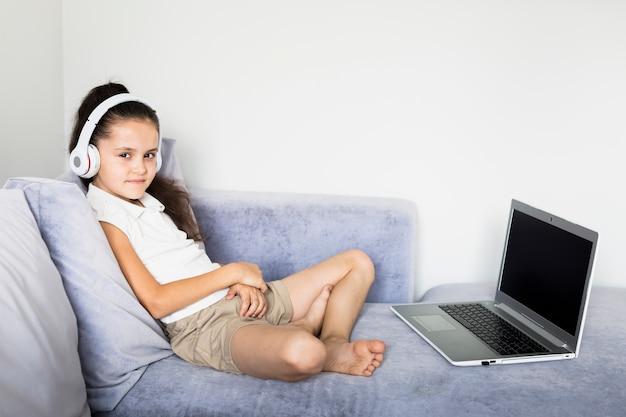 Niña pequeña adorable usando su ordenador portátil