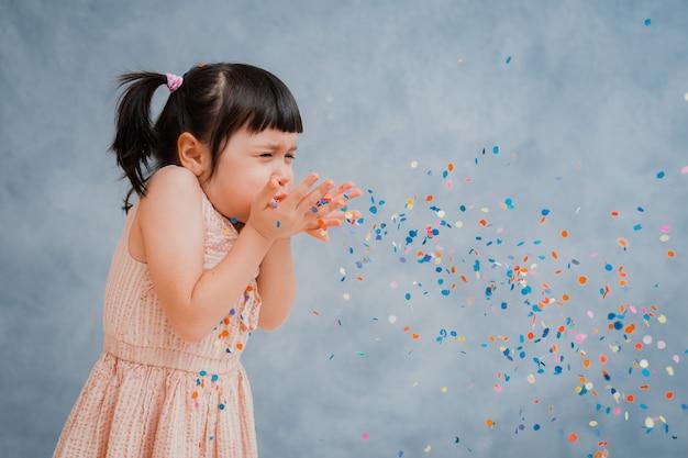 Niña pequeña alegremente arroja coloridos guirnaldas y confeti.