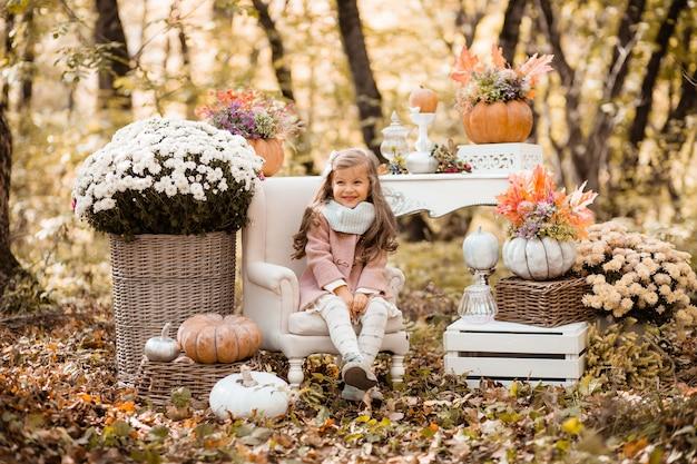 Niña pequeña en el bosque de otoño